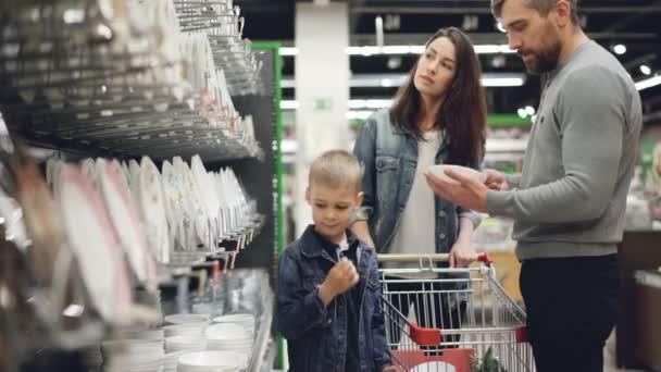 Usmívající se rodina kupuje misky a talíře v oddělení nádobí v hypermarketu, oni jsou pokrmy z police a do nákupního vozíku.
