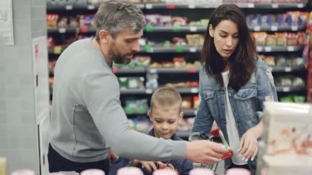 Mladé rodiny matka, otec a dítě a volbou sladkosti v obchod s potravinami, přičemž výrobky a při pohledu na ně pak uvedení vozíku. Police s chutné potraviny jsou viditelné