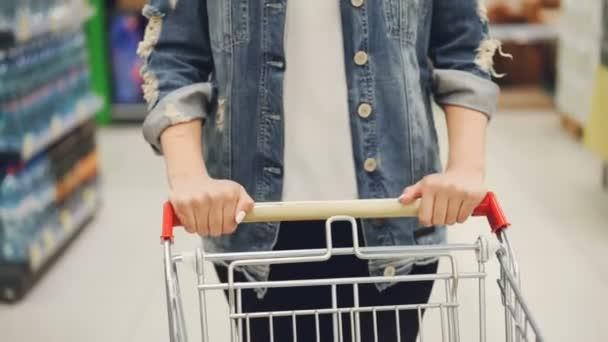 Close-up shot z ženských rukou tlačí nákupní vozík v supermarketu, police s jídlem a nápoji jsou viditelné. Nákup a výběr produktů a lidé koncepce
