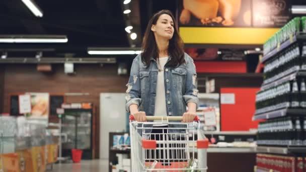 Krásná dáma v neformálním oblečení chodí v obchodu s potravinami řízení nákupní vozík s jídlem uvnitř a rozhlížel se police s produkty. Koncept ženy a obchody