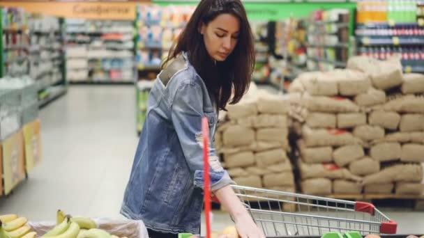 Hezká žena spokojený zákazník nekupuje ovoce v supermarketu banány a jablka a vložením do nákupního košíku. Zdravý životní styl a obchody koncept