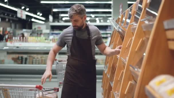 Male employee of large supermarket is taking fresh bread from shopping cart and putting it on shelves in bakery department. Selling food and people concept.