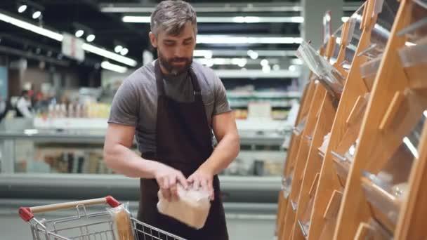 Práce prodavač je uvedení chleba na policích v oddělení pekárny v obchod s potravinami, vousatý chlap nosí zástěru. Prodej výrobků, povolání a koncepci obchodu
