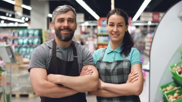 Porträt zweier Supermarktangestellter attraktive Menschen in Schürzen, die im Laden stehen, lächeln und in die Kamera schauen. Regale mit Speisen und Getränken sind sichtbar.