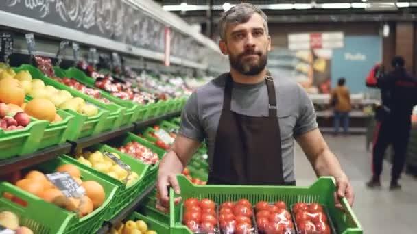 Dolly záběr mladý prodavač v zástěře přepravní box rajčat v supermarketu v oddělení ovoce a zeleniny. Prodejce, koncept store a prosefession potravin