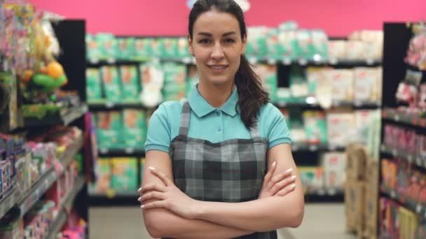Portrét atraktivní mladá prodavačka v zástěře stojí v supermarketu s rukama-překřížené, při pohledu na fotoaparát a usmívá se. Obchodní podnikání a lidí koncepce