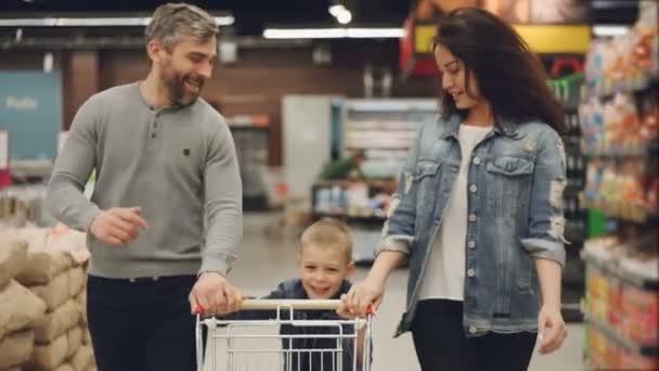 Zpomalený pohyb veselé lidi šťastné rodiny běží v obchod s potravinami s nákupního vozíku a smál se, chlapec je tlačí vozík a jeho rodiče mu pomáhají