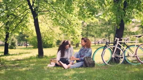 Pretty Caucasian girl is talking to her African American friend and laughing during break after riding bicycles, young women are sitting on lawn in park and chatting.