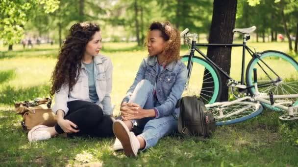 Americká dívka mluví s kamarádkou kavkazských sedí na trávníku v parku, moderní kola a batohy jsou viditelné. Smíšené rasy přátelství a konverzace koncepce.
