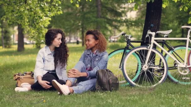 Pretty African American woman is talking to her European friend in park sitting on grass, girls are chatting and laughing. Bikes and trees are in background, sunny day.