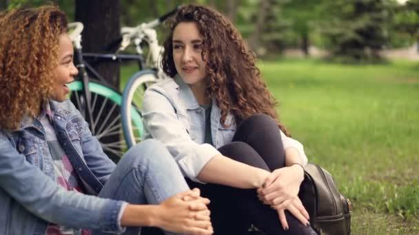 Veselý mladé ženy turisté jsou chatování a smáli se, sedí na trávníku v parku po aktivně stráveném dni na kolech. Šťastní lidé, krásná příroda a konverzace koncepce