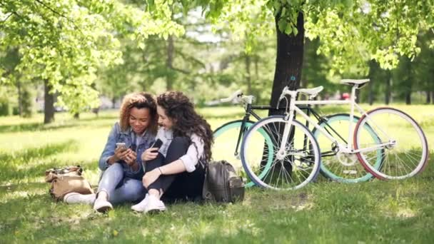 Cheerful young women Caucasian and African American are talking and using smartphones in park, girls are watching screen and laughing. Bicycles are in background.