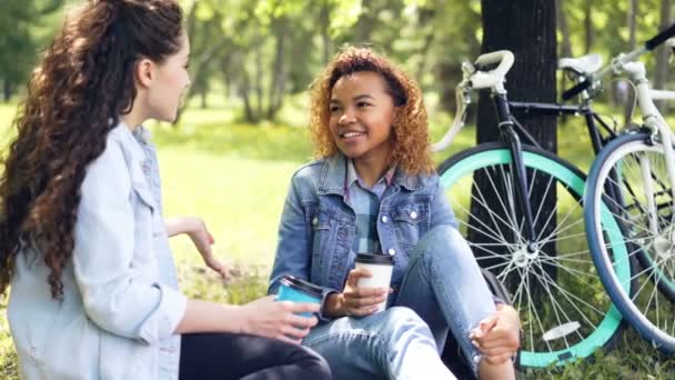 Two female cyclists are having rest drinking coffee sitting on lawn in park and chatting after riding bikes. Active lifestyle, modern young people and leisure concept.
