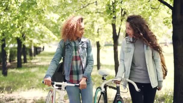 Dolly atış bisikletleri rahatlatıcı ile parkta yürüyüş bisiklet sürme ve sosyalleşme sonra neşeli kız arkadaş. Çok ırklı dostluk, hobi ve aktif yaşam tarzı kavramı.
