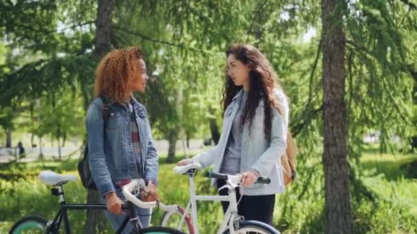 Two pretty female bicyclers with backpacks are talking standing in the park holding bikes. Pan shot of beautiful city park with many trees and green lawns.