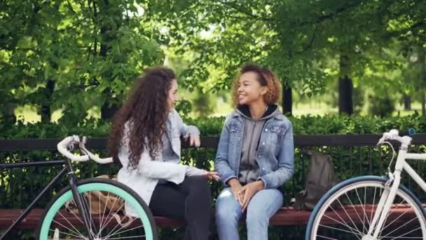 Happy girls are chatting and laughing sitting on bench in park, bikes and backpacks are visible. Modern lifestyle, urban people and recreational area concept.