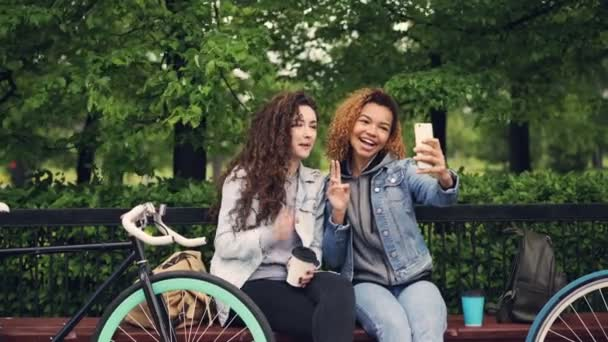 Female friends are taking selfie with smartphone sitting on bench in park holding coffee, young women are posing with silly faces having fun enjoying free time.