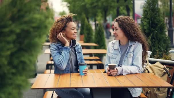 Cheerful young women best friends laughing and talking while sitting at table in outdoor cafe and drinking coffee, girls are socializing and having fun discussing news.