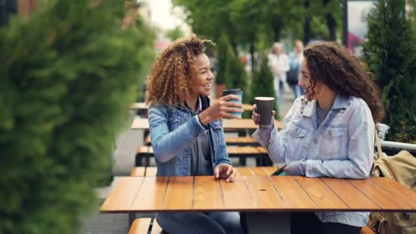 Pretty young women are toasting and clinking coffee cups then drinking coffee and talking while resting in outdoor cafe in city park. People are walking in background.