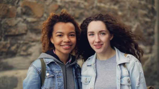 Két csinos, fiatal nő meg állt össze közelében kőfal, és mosolyogva néz a kamera közeli portréja. Vegyes verseny barátság és az emberek koncepció.
