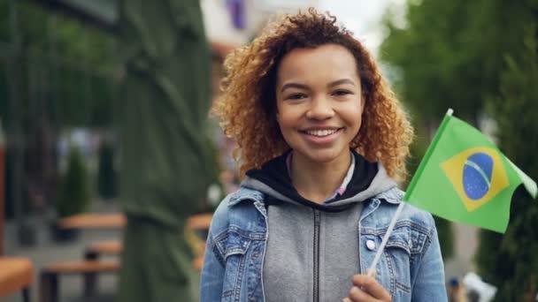 Slowmotion portrét afroamerické ženy šťastné turisty při pohledu na fotoaparát, usmívající se a podržením brazilskou vlajkou stojí venku. Cestovní ruch a lidé koncepce.