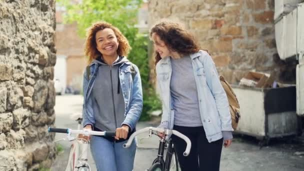 Slowmotion of happy Caucasian and African American girls tourists laughing and walking with bicycles along street with old buildings. Tourism and people concept.