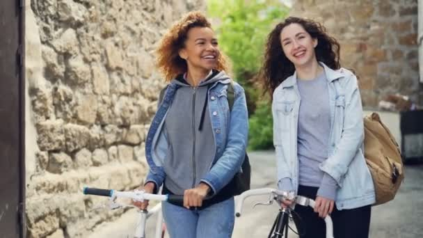 Slowmotion of happy attractive young women tourists laughing and walking with bikes along street with beautiful old buildings. Tourism and people concept.
