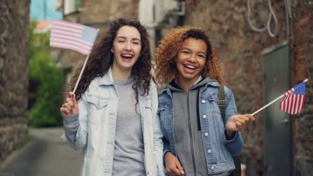 Slowmotion portrait of two pretty girls in casual clothing waving American flags and laughing looking at camera. Friendship, tourism and happy people concept.