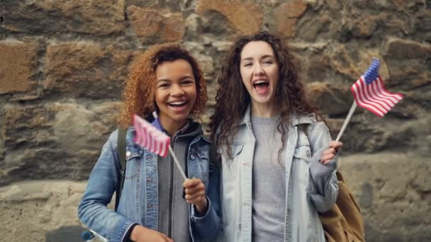 Slow motion portrait of two friends pretty young women in casual clothes waving American flags and laughing looking at camera. Friendship, tourism and happy people concept.