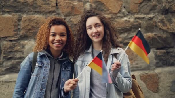 Slowmotion portrait of two smiling girls friends waving German flags and looking at camera standing against stone wall. Friendship, tourism and happy people concept.
