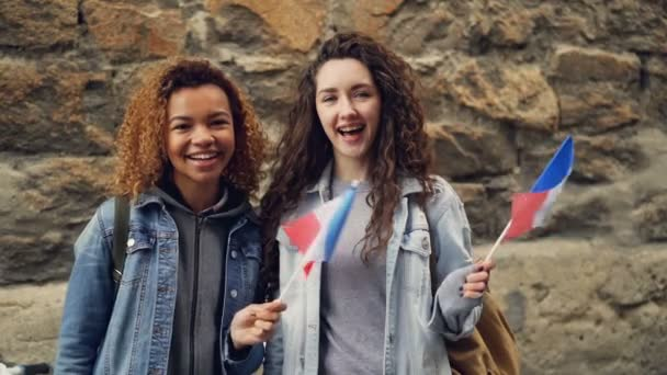 Slowmotion portrait of two laughing women students waving French flags and looking at camera standing against brickwall. Friendship, tourism and happy people concept.