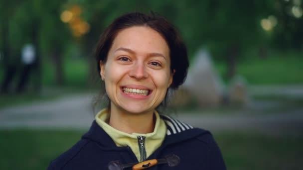 Zpomalený pohyb portrét okouzlující mladá žena nosí ležérní oblečení stojí venku v parku a usmívá se, při pohledu na fotoaparát. Lidé, příroda a koncept zdravého životního stylu