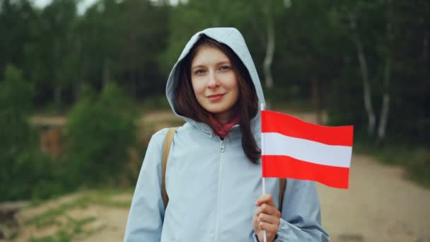 Slow motion portrait of pretty Austrian lady proud citizen holding flag of Latvia, smiling and looking at camera. Nationality, travelling around the world and people concept.