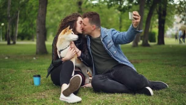 Pohledný mladý muž bere selfie s jeho přítelkyní, který drží rodokmenu psa, chlap je líbat holku a pak sledovat fotografie na obrazovce, lidé se smějí.