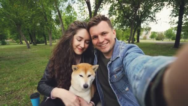 Young wife and husband are taking selfie with adorable dog kissing and hugging each other and the animal. Point of view shot of happy people, pet and green park.