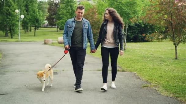 Dolly záběr veselé lidi studenti venčení psa v městském parku, guy vede psa a držela ho za ruku přítelkyně. Krásné zelené trávy a stromy jsou kolem.