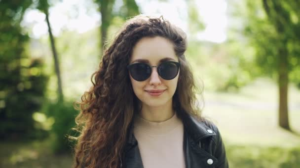 Portrait of attractive woman in sunglasses and trendy leather jacket looking at camera and smiling standing in city park on summer day. People and sunlight concept.