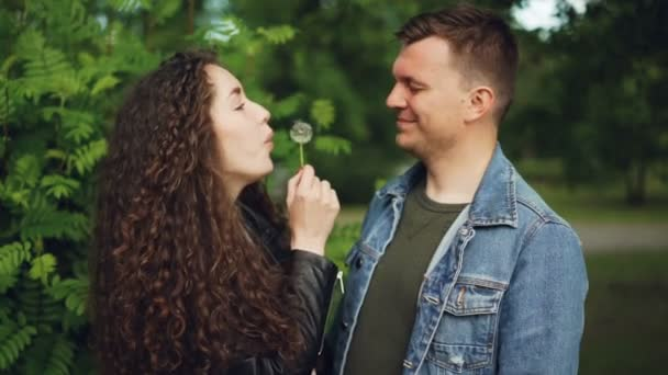 Slow motion of cute couple husband and wife having fun in the forest, girl is blowing dandelion blowball in mans face, he is smiling and closing eyes.