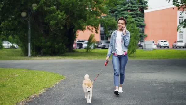 Happy Smíšené rasy dívka chodí pes v parku a mluví o mobilní telefon komunikovat s přáteli. Moderní technologie, milující zvířata a komunikační koncept.