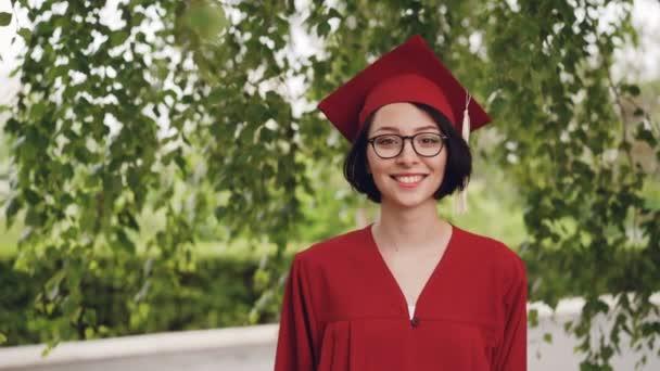Portré örömteli fiatal nő szigorló ruha-és habarcs- és mosolyogva néz a kamera állandó Campus a fa alatt. Ifjúsági és oktatási koncepció.
