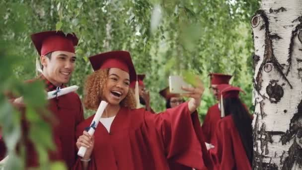 Happy young people girl and guy are taking selfie after graduation ceremony holding diplomas wearing gowns and mortarboards. Photographs and education concept.