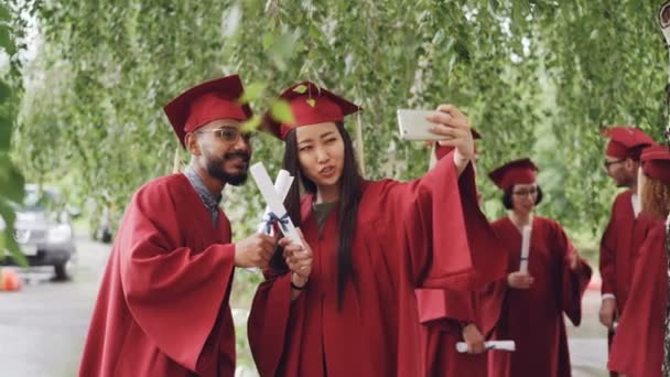 Fellow students are taking selfie with diplomas posing and smiling, girl is holding smartphone, people are wearing gowns and hats. Education and modern lifestyle concept.