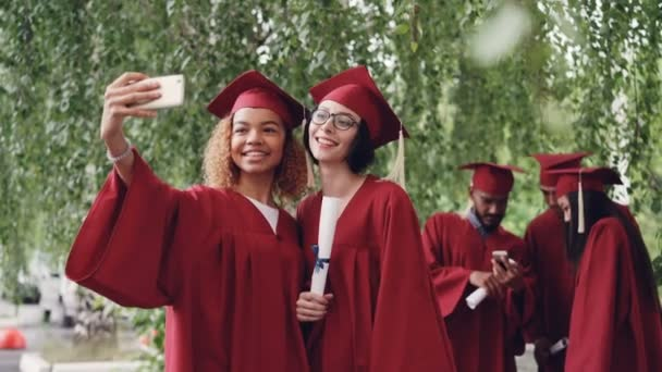 Pretty female graduates are taking selfie with diploma scroll using smartphone, young women are posing with other students in gowns moving and talking in background.
