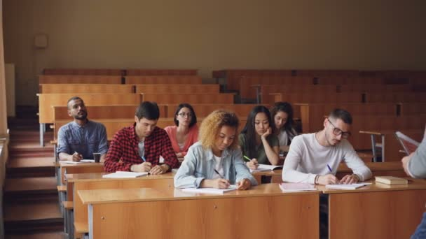 Professor is reading lecture to group of multiracial students standing in classroom with papers and speaking while young people are listening to him and writing sitting at desks.