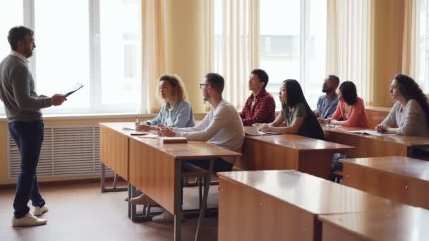 Přátelský učitel mluví studentům klást otázky, zatímco mladí lidé jsou zvyšování rukou a odpovídání na posezení u přepážek. Střední školy, vzdělávání a mládež koncepce
