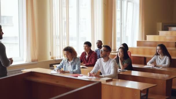 Chytrý člověk student je zvyšovat ruku a mluví profesor, zatímco spolužáci jsou naslouchat jim a usmíval se. Žák a učitel vztahy koncepce.