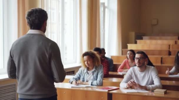 Férfi tanár elmagyarázza új információ több etnikai csoport, a diákok, akik írásban notebook beírnak. Szakmai, oktatási és ifjúsági koncepció.