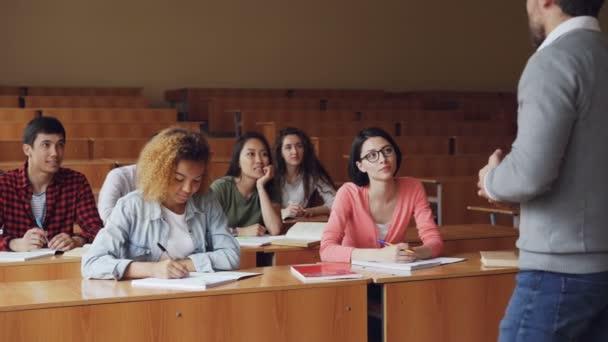 Studenty středních škol mají lekci s muž učitel, mladí lidé jsou psaní a mluvící Tutor sezení u stolů. Milénia, vysokoškolských institucí a koncepce školy