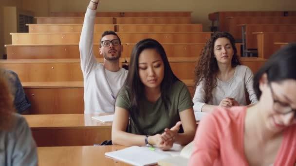 Samec studenta je zvyšovat ruku a žádají otázku pak poslouchat odpověď, mladých lidí, kteří sedí kolem něj jsou při pohledu na učitele a pořizování poznámek.