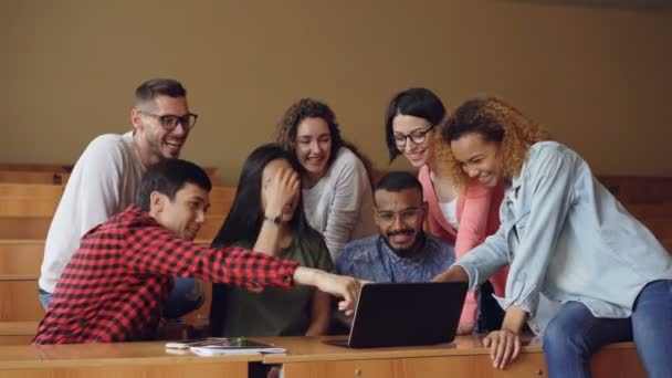 Cheerful men and women are working with laptop looking and pointing at screen, talking and laughing sitting at desks in university lecture hall. Students and technology concept.